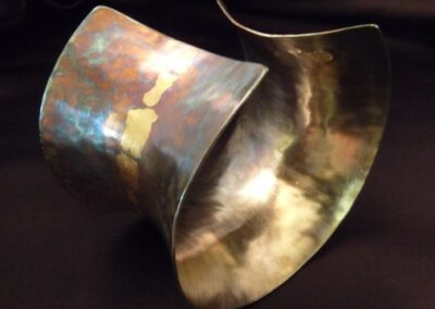 Wide anti-clastic cuff in oxidised sterling silver gilded with 22ct gold accents.  The gold is fused onto the silver using the ancient Korean technique of Keum-boo which uses only heat and pressure to bond the two metals.  The cuff is then oxidised until the desired shade is reached - yellow, green, red, blue or in this case, purple.  The inner surface is highly polished for contrast and shine and a high quality wax is then applied to protect the surface from further oxidisation.  Available in sterling silver only from £340.00 (ref. wws-02)