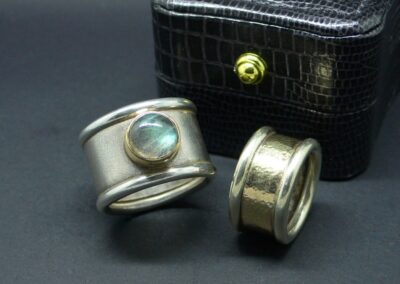 Bold and striking, heavyweight sterling silver ring with a frosted, matt finish and a stunning Labradorite cabochon bezel-set in polished 9ct yellow gold for contrast.  Known as a healing stone, Labradorite is said to protect one from negativity and misfortune.  From £366.00 (ref. gsrl-02).  Also shown - plain band ring of 9ct yellow and white gold, see separate image for details.