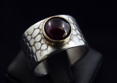 Contemporary sterling silver ring with embossed snakeskin finish and a stunning garnet bezel-set in 9ct yellow gold.  From £205.00 (ref. gsrg-03)