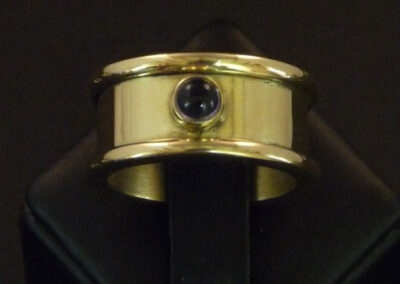 Striking 18ct yellow gold ring with a highly polished finish and a bezel-set iolite cabochon.  Also known as Water-Sapphire, iolite was used by the Vikings as a polarising filter so that they could determine the exact location of the sun.  In shifting shades of violet-blue, this gemstone is said to restore a sense of perspective to those who feel they are jinxed and restores order out of chaos!  From £1,890.00 (ref. gsri-01)